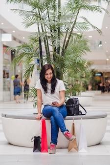 Mulher sentada no shopping olhando para o celular e sorrindo, com algumas sacolas de compras no chão.