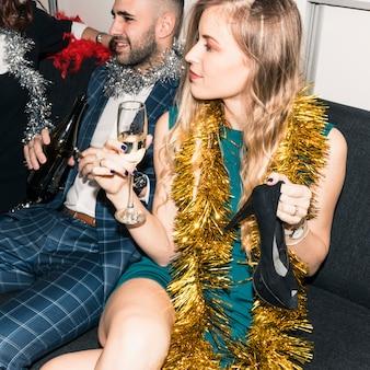 Mulher sentada no sofá com uma taça de champanhe