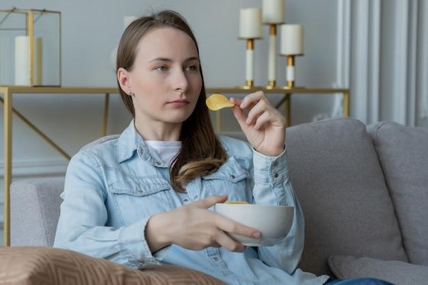 Mulher sentada no sofá comendo batata frita