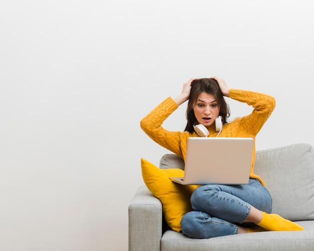 Mulher sentada no sofá cometeu um erro no seu laptop