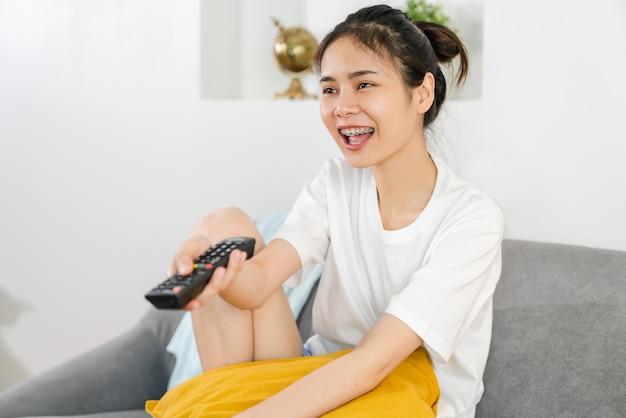 Mulher sentada no sofá e segurando o controle remoto da tv