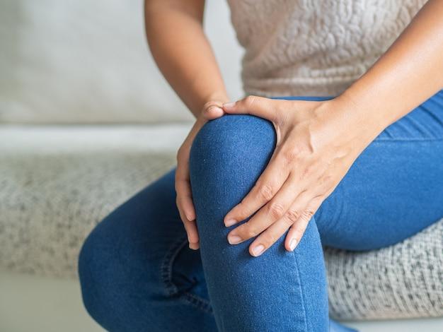 Mulher sentada no sofá e sentindo dor no joelho
