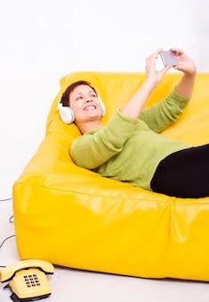 Mulher sentada no sofá e tirar selfies