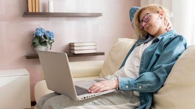 Mulher sentada no sofá e trabalhando no laptop