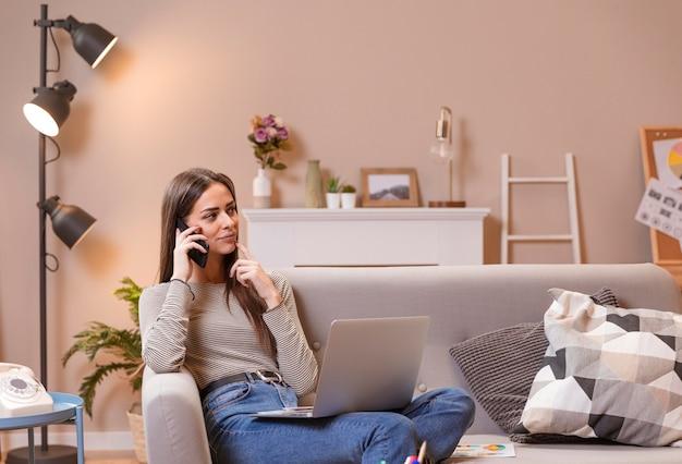 Mulher sentada no sofá e trabalhando
