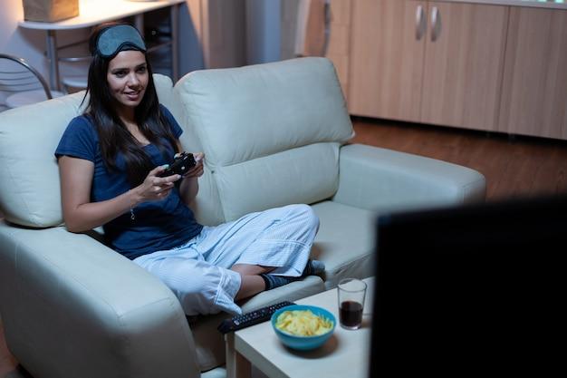 Mulher sentada no sofá jogando videogame tarde da noite usando máscara para os olhos na testa. jogador empolgado e determinado usando joysticks de controle, teclado, jogo de playstation e se divertindo com jogos eletrônicos vencedores