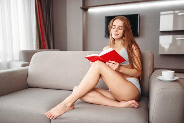 Mulher sentada no sofá lendo o livro