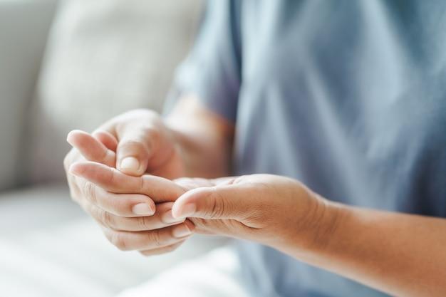 Mulher sentada no sofá segura o pulso, lesão na mão, sentindo dor cuidados de saúde e conceito médico