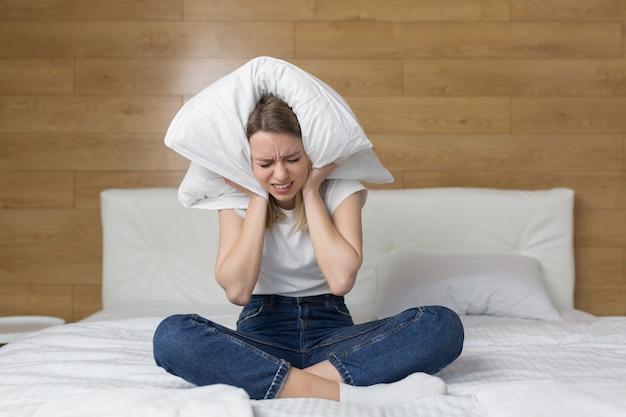 Mulher sentada no sofá tapando as orelhas com as mãos incomodadas com o barulho