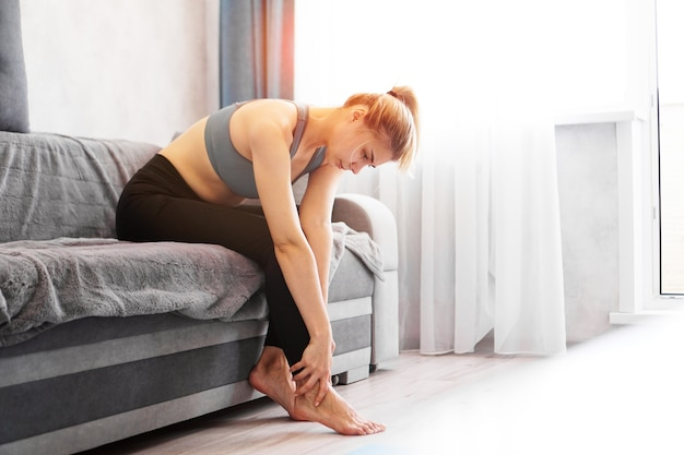 Mulher sentada no sofá tem uma lesão no pé, sentindo dor. cuidados de saúde e conceito médico.