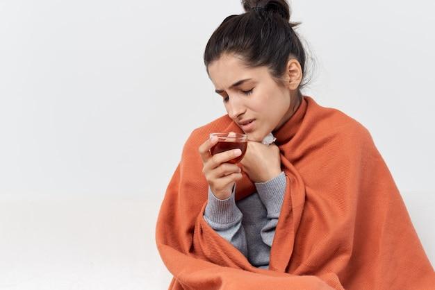Mulher sentada no sofá tomando uma xícara de chá e tratando uma insatisfação fria