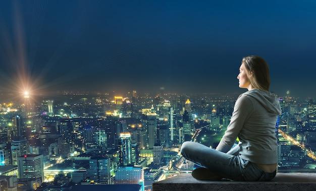 Mulher sentada no telhado com bela vista iluminada da cidade à noite