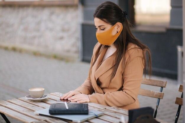 Mulher sentada no terraço com máscara facial. mulher vai beber café ao ar livre. mulher atraente sentado no café durante o intervalo. Foto Premium