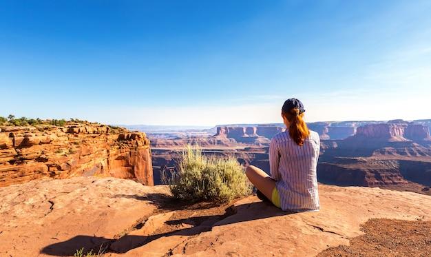 Mulher sentada no topo de uma montanha rochosa