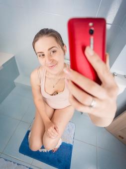 Mulher sentada no vaso sanitário e fazendo selfie no smartphone