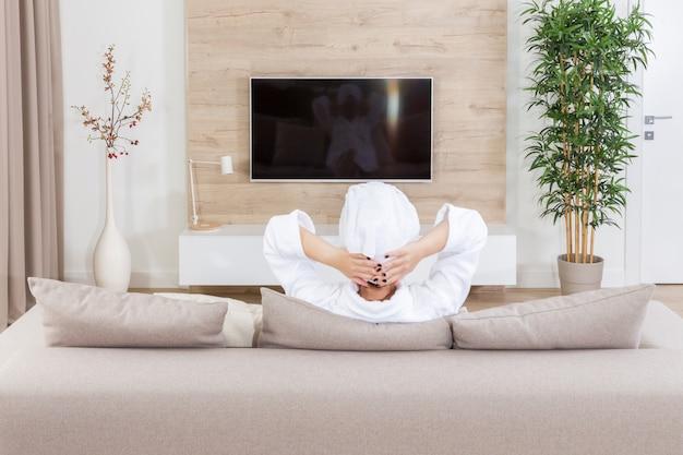 Mulher sentada num sofá com uma toalha na cabeça assistindo tv