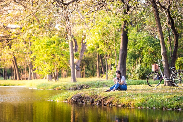 Mulher sentada ouvindo música no jardim ao pôr do sol.