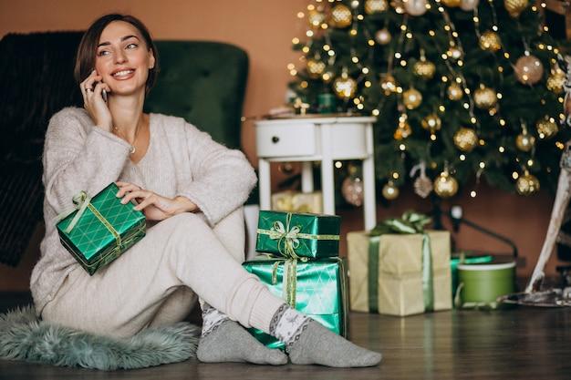 Mulher sentada perto da árvore de natal e fazer compras no telefone