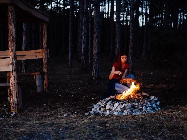 Mulher sentada perto da floresta perto da fogueira