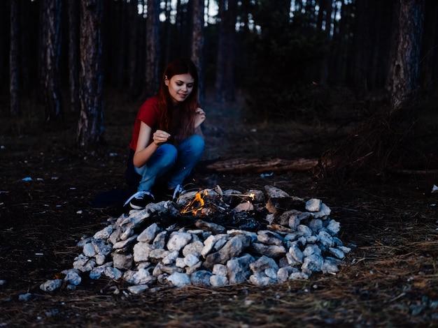 Mulher sentada perto da fogueira à noite de férias na floresta viajar