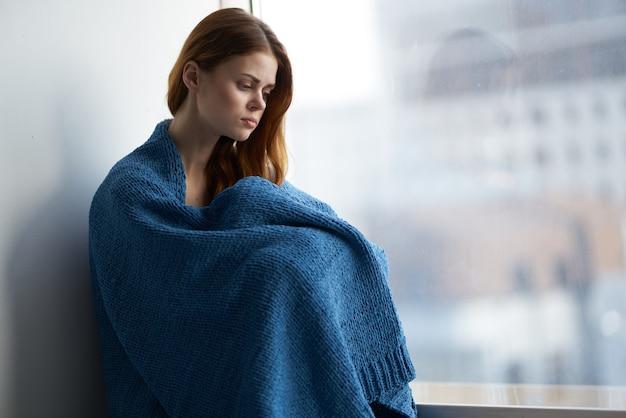 Mulher sentada perto da janela com um sorriso xadrez azul em casa