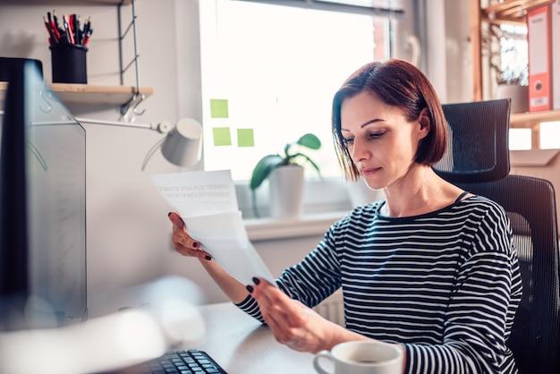 Mulher sentada perto da janela e lendo e-mails no escritório