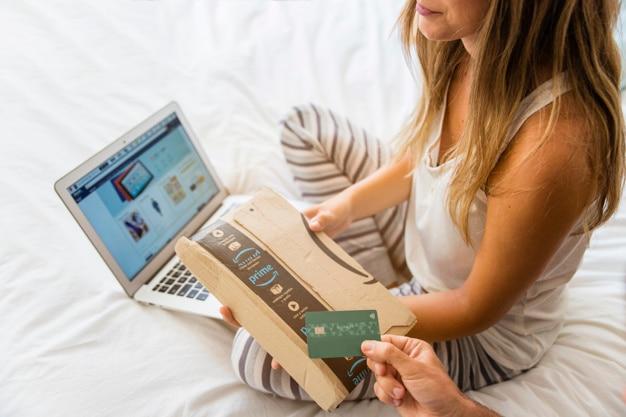 Mulher sentada perto de laptop e mão com cartão de crédito