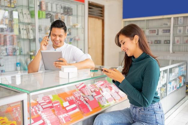 Mulher sentada perto de uma loja enquanto digita uma mensagem usando um telefone celular