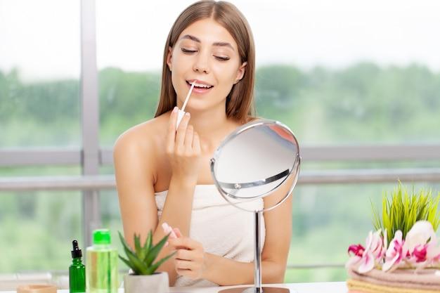 Mulher sentada perto do espelho aplicando maquiagem