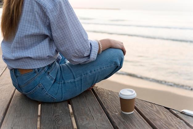 Mulher sentada perto do mar de costas