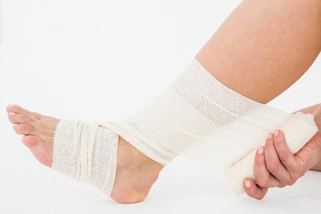 Mulher sentada que bate o tornozelo