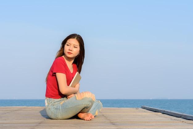 Mulher sentada segurando um livro na ponte de madeira do mar e do céu azul