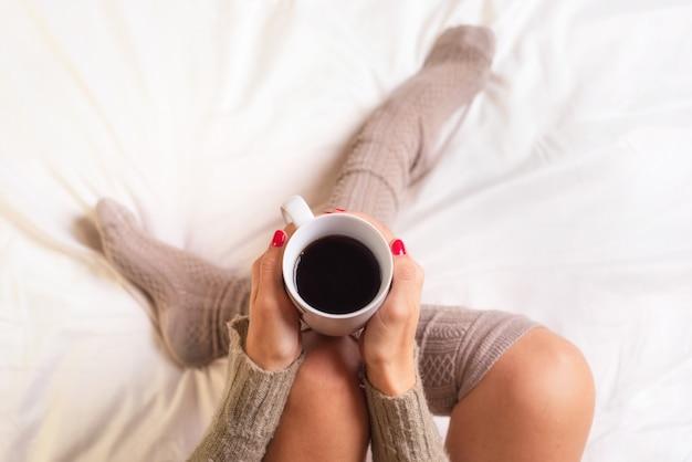 Mulher, sentando, cama, bebendo, um, xícara café