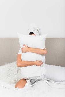 Mulher, sentando, cama, segurando, branca, travesseiro, frente, dela, rosto