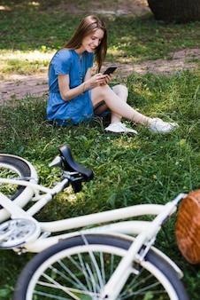 Mulher, sentando, capim, perto, bicicleta