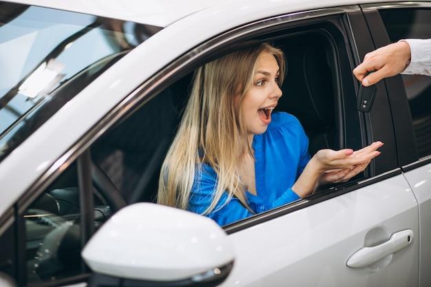 Mulher, sentando, carro, recebendo, teclas, carro, showroom