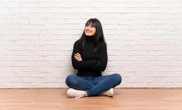 Mulher, sentando, chão, olhar, sorrindo