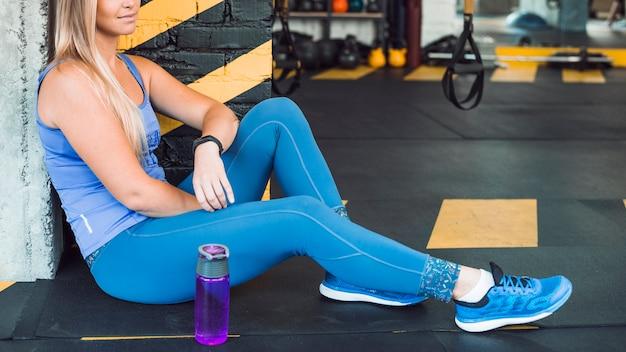Mulher, sentando, chão, perto, garrafa água, em, ginásio