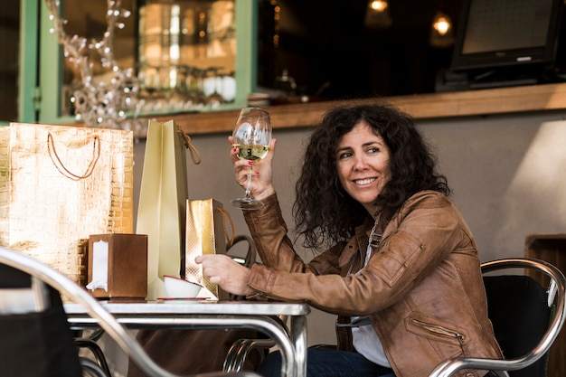Mulher, sentando, com, bolsas para compras, e, vinho