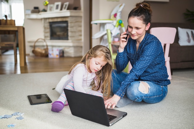 Mulher, sentando, com, dela, filha, falando, ligado, cellphone, enquanto, usando computador portátil