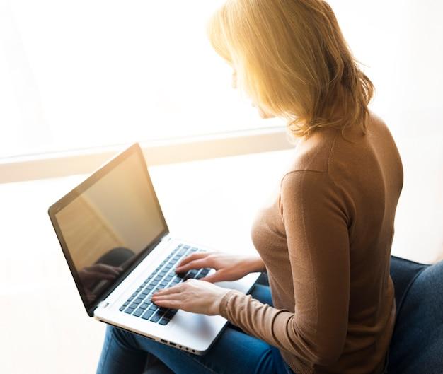 Mulher, sentando, e, usando computador portátil