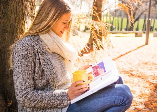 Mulher, sentando, em, parque outono, e, leitura