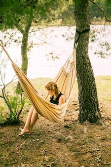 Mulher, sentando, em, rede, ligado, riverbank