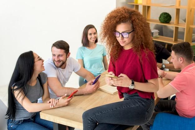 Mulher, sentando, em, tabletop, usando, telefone móvel