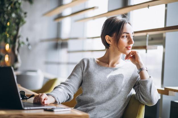 Mulher, sentando, em, um, café, café bebendo, e, trabalhar, um computador
