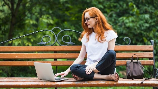 Mulher, sentando, ligado, banco, com, laptop