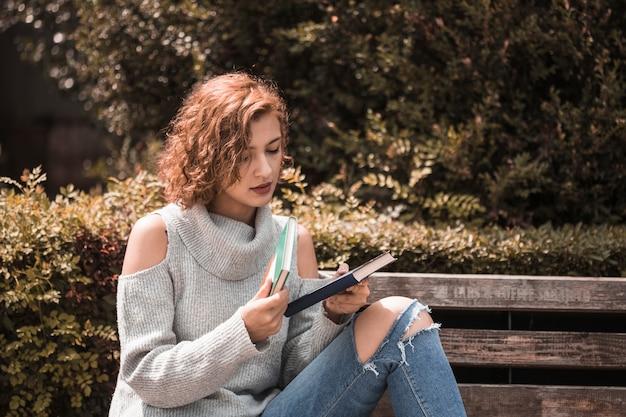 Mulher, sentando, ligado, banco, e, segurando, livros