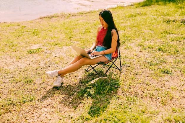 Mulher, sentando, ligado, cadeira, ao ar livre, com, laptop