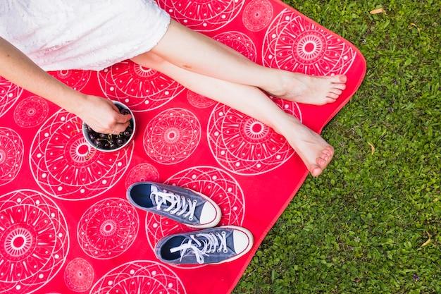Mulher, sentando, ligado, cobertor vermelho, segurando, cereja, sobre, a, grama verde