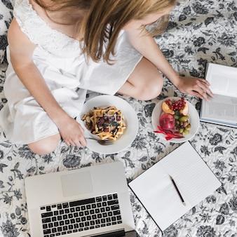 Mulher, sentando, ligado, floral, cama, com, waffle, e, frutas, pequeno almoço, livro leitura